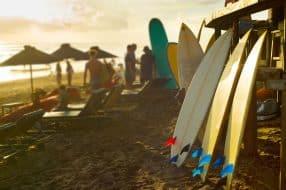 Surf à louer sur la plage de Bali au coucher du soleil