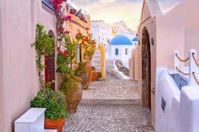 Étroite rue pittoresque d'Oia Village sur l'île de Santorin au coucher du soleil, Grèce.