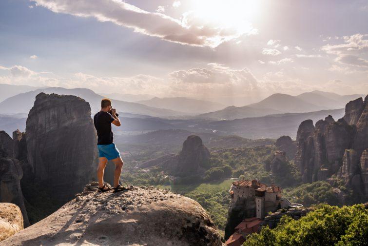 Homme prenant une photo des Monastères des Météores, classés au patrimoine mondial de l'UNESCO, Grèce