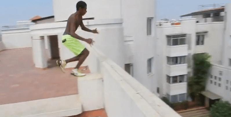 Un jeune saute dans une piscine depuis le toit d'un hôtel