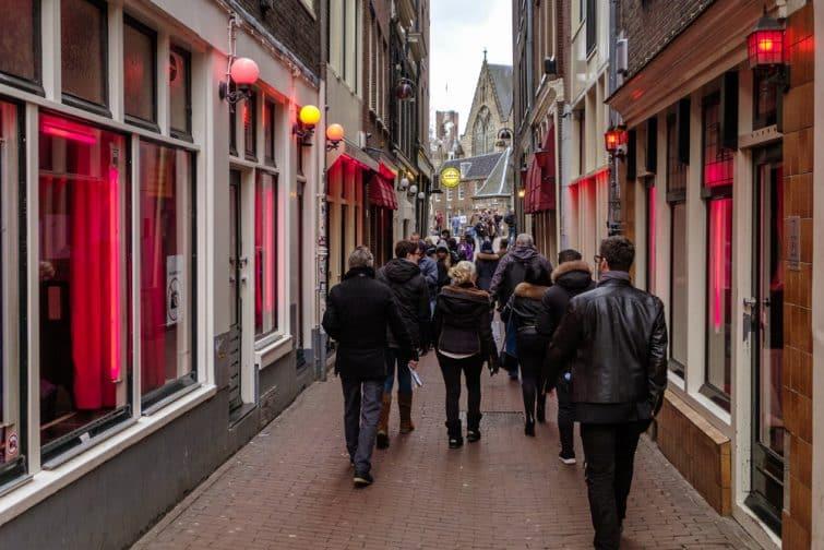 Touristes marchant dans les rues du Quartier Rouge à Amsterdam
