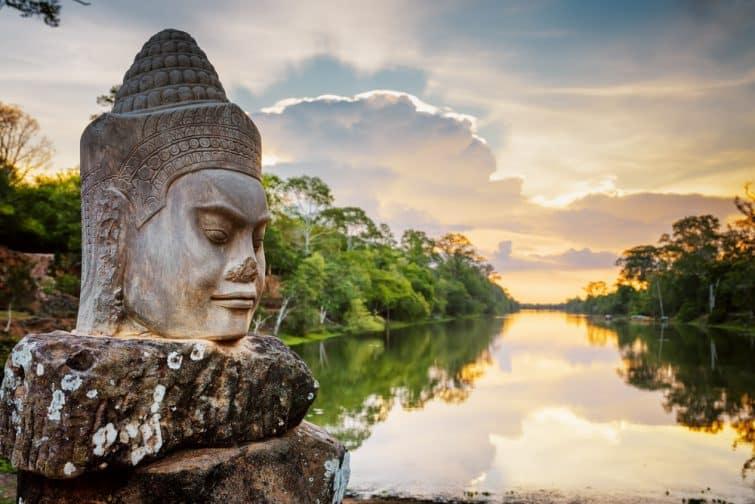 Face de pierre Asura sur la route de la porte sud d'Angkor Thom à Siem Reap, Cambodge. Bel coucher de soleil sur une ancienne douve sur fond gris