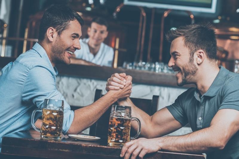 amis qui font un bras de fer en buvant une biere a paris