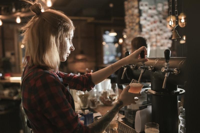 Bartender qui travaille. où deguster une bière à paris