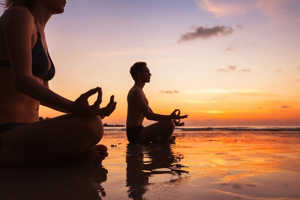 couple qui fait du yoga en france ocean atlantique au bord de mer coucher de soleil
