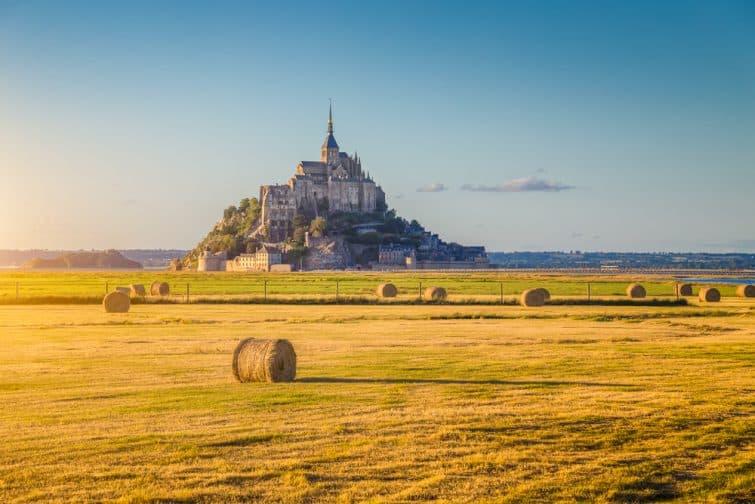 Belle vue sur l'île de marée du Mont Saint-Michel, belle lumière dorée le soir au coucher du soleil en été avec des balles de foin sur les champs vides, Normandie, Nord de la France