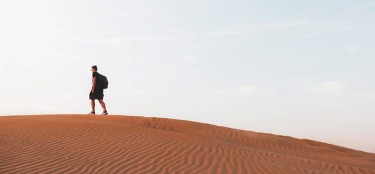 Homme qui marche dans le désert de Dubaï