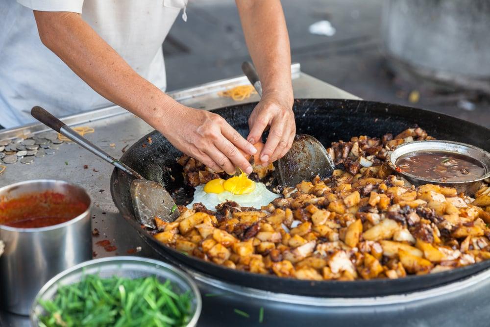 Homme préparant de la nourriture de rue en Malaisie