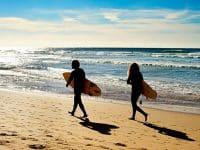 Couple of surfers walking on the ocean beach. Sagres, Algarve, Portrugal