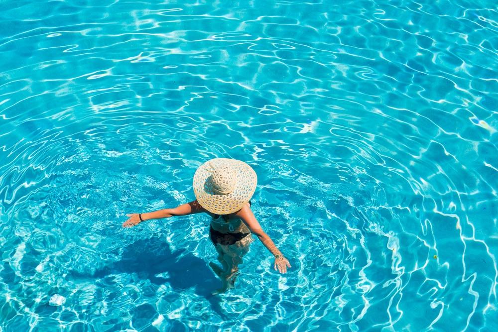 Jeune femme en bikini portant un chapeau de paille à la piscine