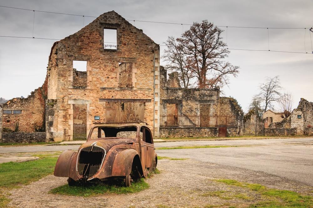 Maison en ruine et carcasse de voiture à Oradour-sur-Glane