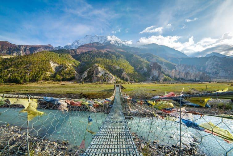 Pont de suspension avec drapeaux bouddhistes pour la prière sur le circuit d'Annapurna au Népal. Shangri-la