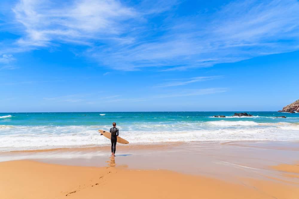 Surfer sur la plage de Praia do Amado par beau temps, région de l'Algarve, Portugal