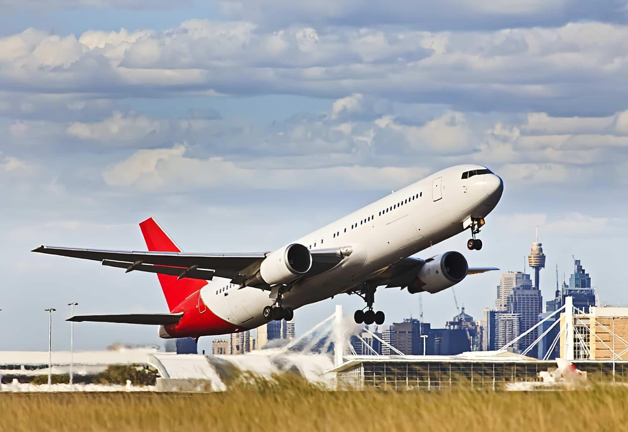 Un avion de ligne moderne décollant de l'aérodrome de l'aéroport contre les immeubles CBD de Sydney et les tours vers le ciel bleu.