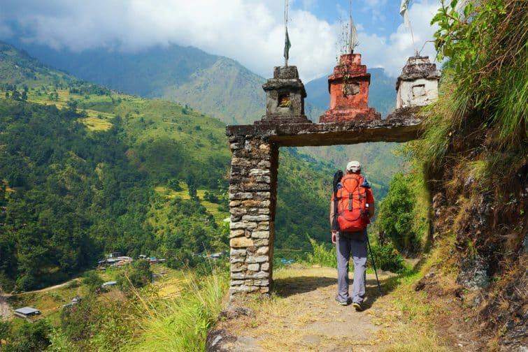Un homme, entre la porte du village népalais dans la vallée sur le circuit d'Annapurna Trek