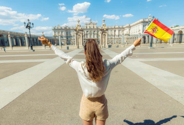 Vue d'une femme derrière la mode avec le drapeau espagnol se réjouissant contre le Palais Royal