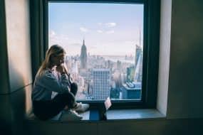 Jeune femme en train de travailler avec vue sur New York