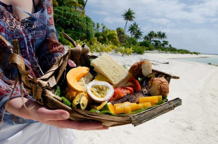 Les mains d'une jeune femme transportent des aliments tropicaux de poissons grillés, fruits et légumes servis sur l'île tropicale déserte de la lagune d'Aitutaki, aux Îles Cook.