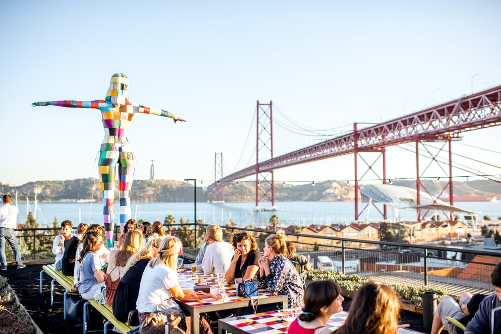 Personnes en terrasse avec pont en fond, Lisbonne