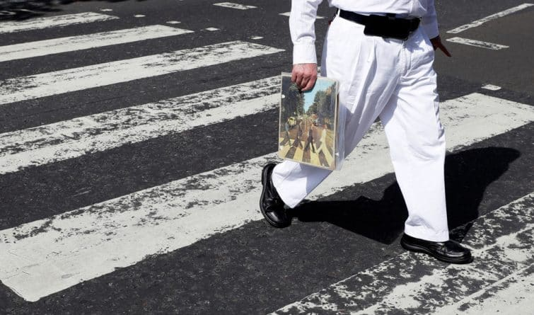 Personne traversant Abbey Road avec une pochette vinyle des Beatles à la main