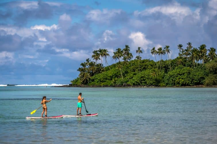 Couple fausant du stand up paddle à Muri Beach, Îles Cook