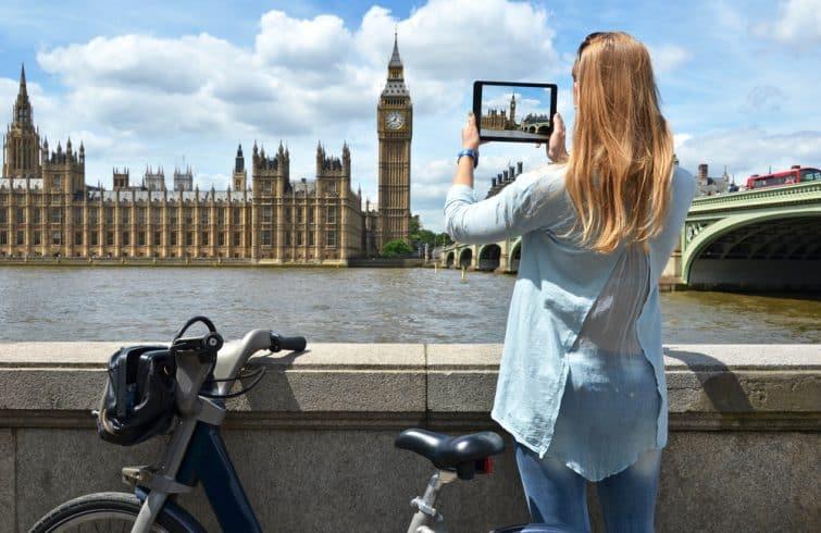 Jeune femme au bord de la Tamise qui prend le Big Ben en photo