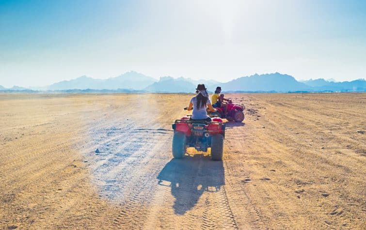 Les touristes font des quads à travers le désert du Sahara jusqu'au village bédouin, en Egypte.