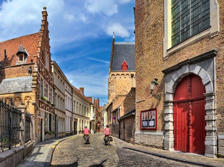 Personnes à vélo dans les rues de la vieille ville à Bruges