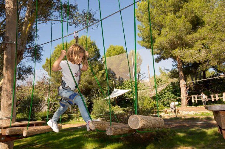 Enfant faisant un parcours d'accrobranche à Jungle Parc, Majorque