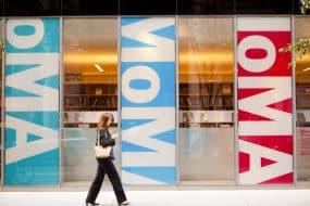 Jeune femme marchant devant la devanture du MoMa à New York