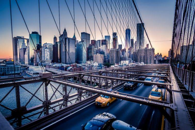 Des voitures qui foncent au coucher du soleil sur le pont de Brooklyn