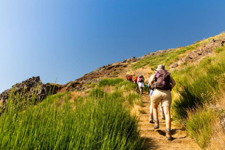 Groupe de touristes grimpant en montagne, Portugal, Madère