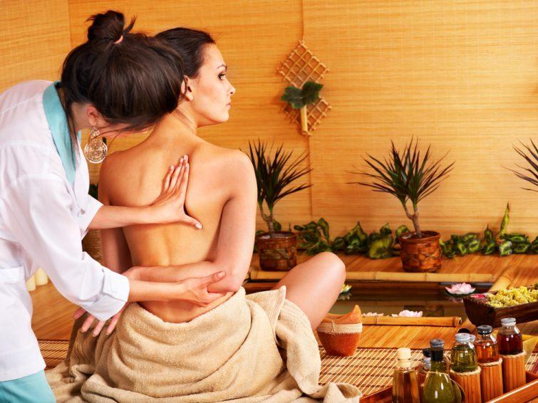 Jeune femme se faisant masser dans un spa en bambou.