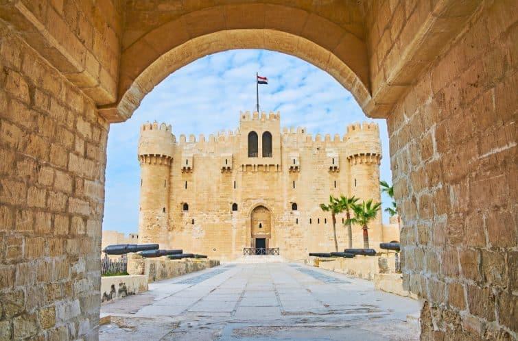 Numéro de la photo de stock libre de droits : 1046395528  La vue sur le fort Qaitbay par sa porte d'entrée en pierre, la ruelle aux canons est vue au premier plan, Alexandrie, Egypte