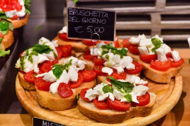 Marché italien: de nombreuses variétés de fromage italien et de fromage français aux olives, à la salade et au bacon, sur les plaques noires, portent des noms de fromages et de prix