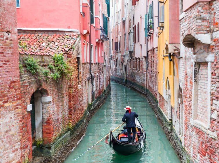 gondolier vénitien punissant la gondole à travers les eaux vertes du canal de Venise Italie