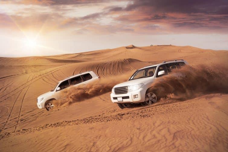 deux véhicules 4x4 se balançant côte à côte dans les dunes du désert le soir au soleil