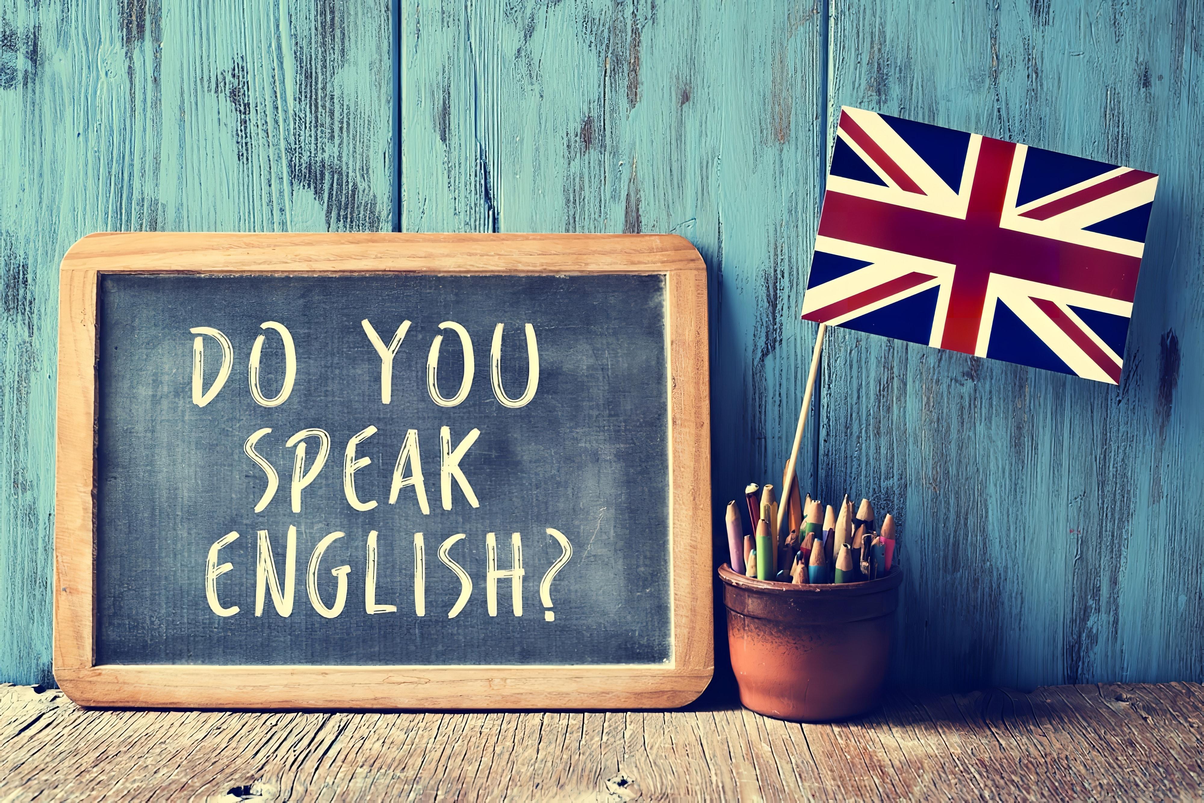 un tableau de bord avec le texte parlez-vous anglais écrit dedans, un pot avec crayons et le drapeau du Royaume-Uni, sur un bureau en bois, avec un effet filtre