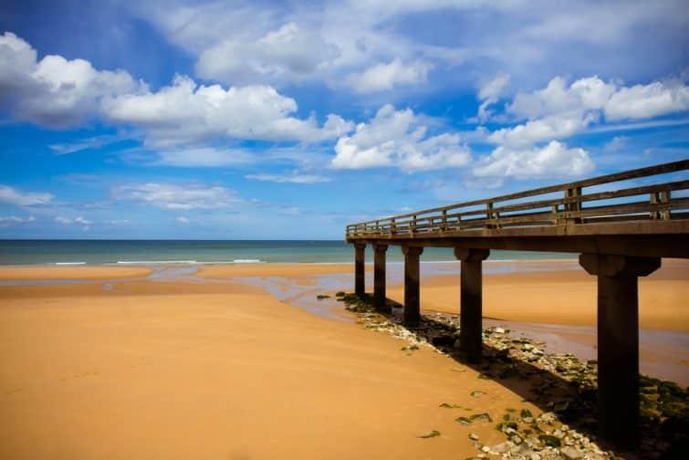 un vieux quai se jette sur la plage de sable de la côte normande, en France, où les alliés débarquent le jour J (6 juin 1944) pendant la Seconde Guerre mondiale