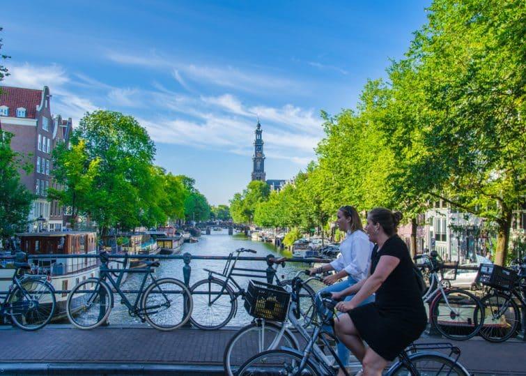 Visiter Jordaan : Femmes sur un vélo traversant un pont à Amsterdam