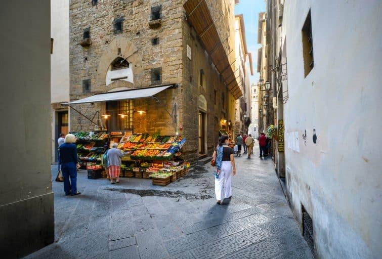 Ruelle commerçante de Florence avec un stand de fruits et légumes