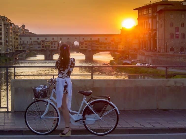 Touriste à vélo prenant en photo le coucher de soleil à Florence