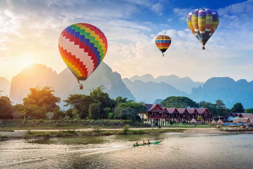 Ballon à air chaud au-dessus de la rivière Nam Song au coucher du soleil à Vang vieng, Laos.
