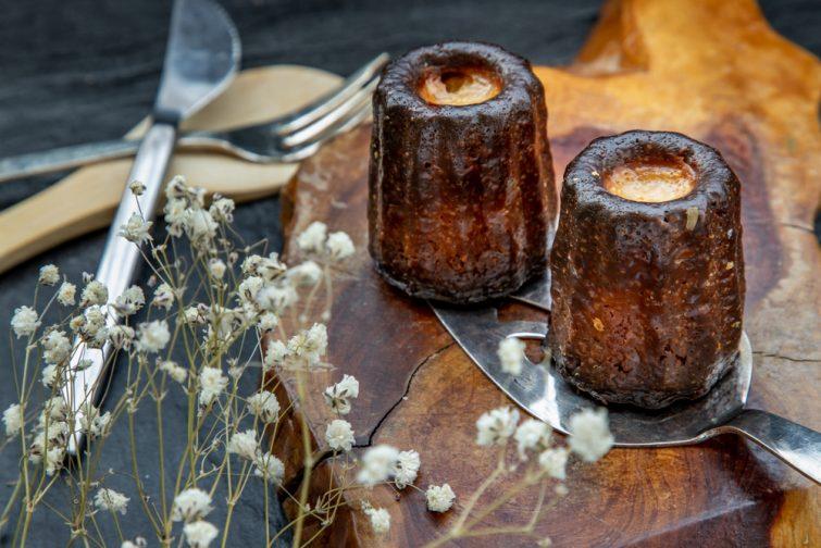 Cannelés de Bordeaux : petite pâtisserie au rhum et à la vanille sur une assiette en bois