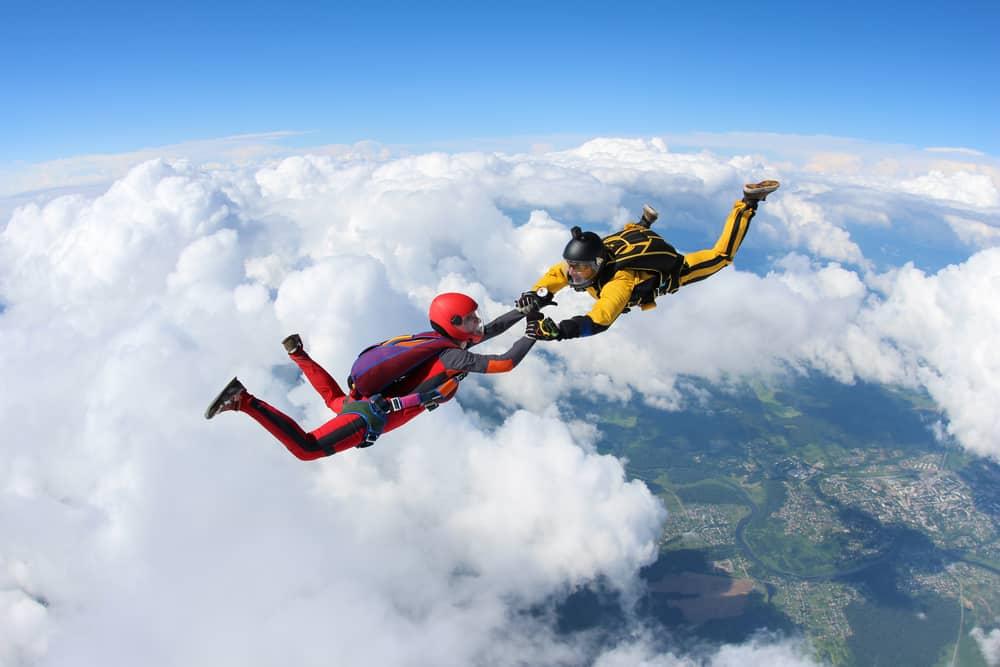 Deux parachutistes tombent sur fond des nuages blancs.