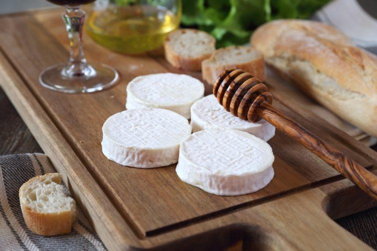 spécialités d'Occitanie Fromage de chèvre doux Rocamadour, pain, miel, laitue et verre de vin rouge. Focus