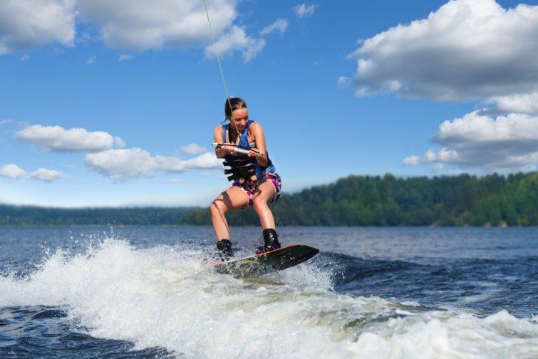 Jeune femme joliment brunette faisant du wakeboard sur une vague de bateau à moteur dans un lac d'été