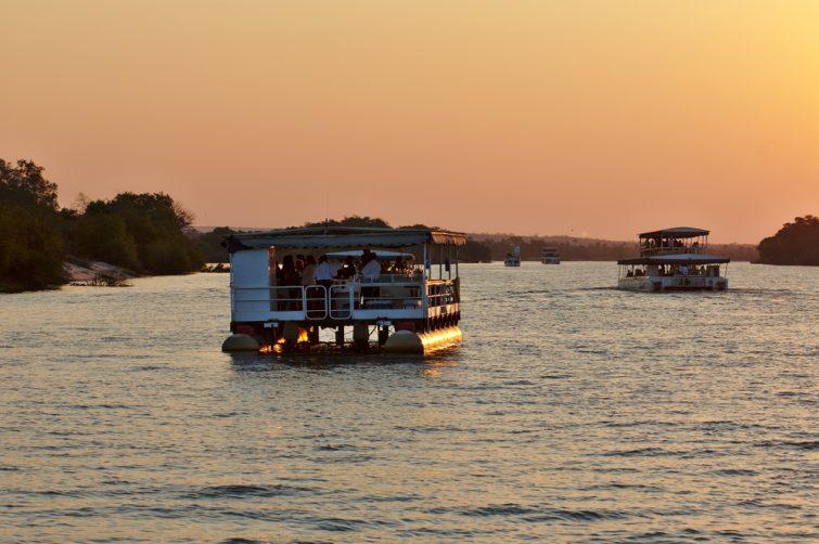 Deux bateaux safari traversant le Zambezi au coucher du soleil. Victoria Falls, Zimbabwe Afrique.