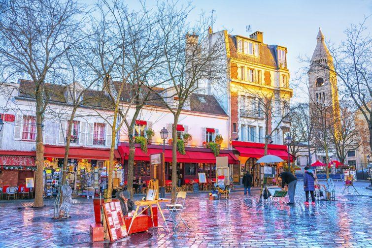 Place du Tertre à Montmartre à Paris. Dans la région beaucoup de souvenirs et d'artisanat. Dans les petites maisons se trouvent des cafés, des restaurants et des galeries d'art.