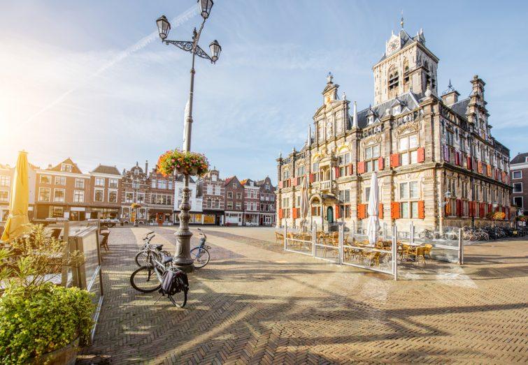 Vue sur l'hôtel de ville et de beaux bâtiments sur la place centrale pendant la matinée ensoleillée dans la ville de Delft, Pays-Bas